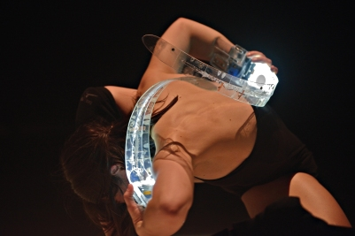 Dancer Soula Trougakos holding two of the Rib digital musical instruments during a performance of Les Gestes. Instrument design by Joseph Malloch and Ian Hattwick. Photograph by Michael Slobodian. Credit: Van Grimde Corps Secrets / IDMIL / CIRMMT / McGill University.